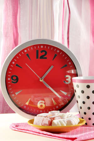 Cup tea and clock on bright background photo