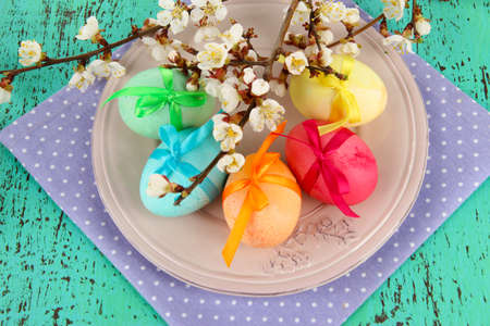 Easter eggs on plate with napkin and flowers on wooden table photo
