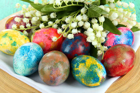 Easter eggs on wooden plate on napkin with flowers close-up photo