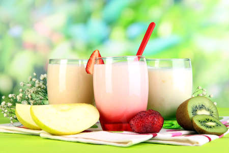 Delicious yogurts with fruits in glasses on wooden table on natural background photo