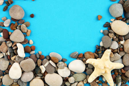 Frame of sea stones on color background photo