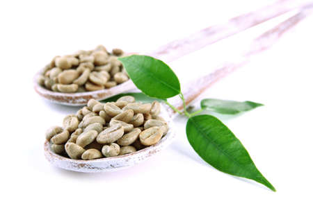 Green coffee beans in wooden spoons and leaves isolated on white photo