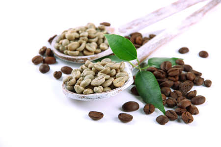Green  and brown coffee beans in wooden spoons and leaves isolated on white photo