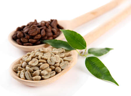unprocessed: Green  and brown coffee beans in wooden spoons and leaves isolated on white Stock Photo