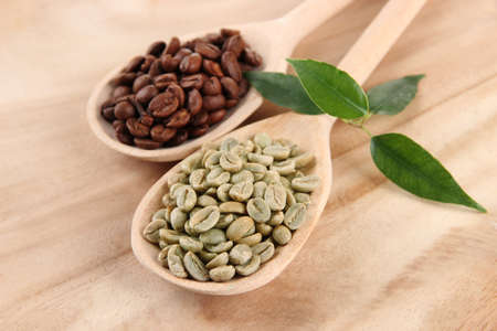 Green  and brown coffee beans in spoons and leaves on wooden background photo