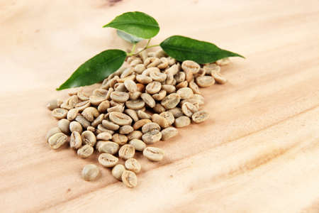 Green coffee beans and leaves on wooden background photo