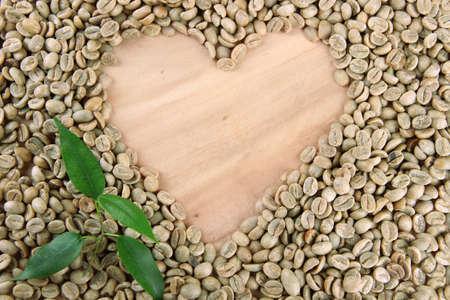 granos de cafe: Granos de caf� verde y hojas sobre fondo de madera