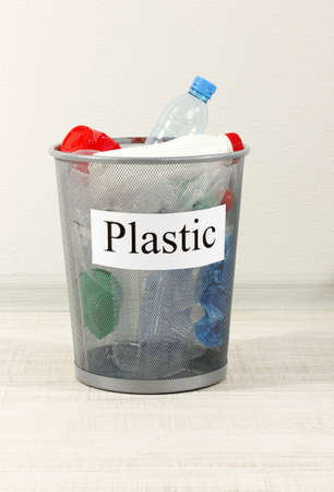 Assorted trash in bucket on room background photo