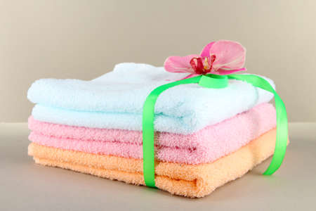 orange washcloth: Towels tied with ribbon on gray background