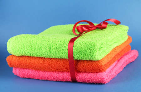 Towels tied with ribbon on blue background photo