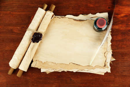 books on a wooden surface: Old paper, ink, scrolls and feather on wooden background