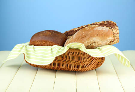 Bread in wicker basket, on wooden table, on color background photo