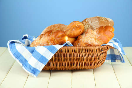 white napkin: Composition with bread and rolls on wooden table, on color background Stock Photo