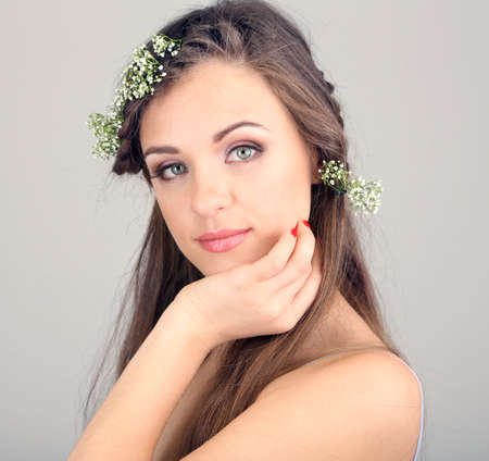 Young woman with beautiful hairstyle and wreath on grey background photo