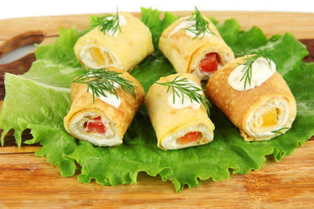 Egg rolls with cheese cream and paprika, on wooden board, close up photo