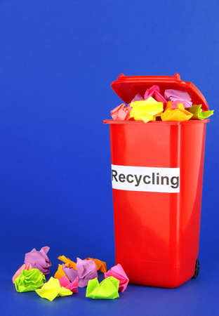 degradable: Recycling bin with papers on blue background