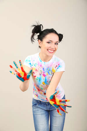 Young pretty painter with hands in paint, on gray background photo