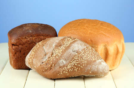 Composition with bread on wooden table, on color background photo