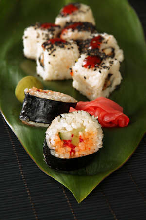 Tasty Maki sushi - Roll on green leaf close-up photo