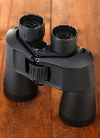 Black modern binoculars on wooden background photo