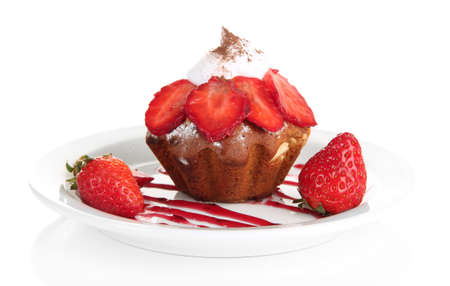 Tasty muffin cake with strawberries and chocolate on plate, isolated on white photo