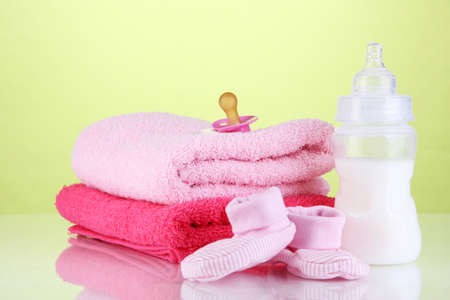 Bottle for milk with towels and nipple on green background photo