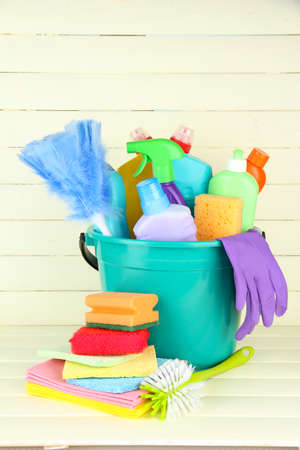 Cleaning items in bucket on  white wooden background photo