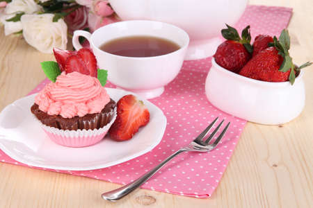 Beautiful strawberry cupcake and flavored tea on dining table close-up photo