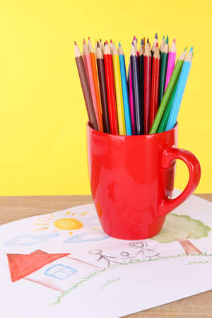 Colorful pencils in cup on table on yellow background photo