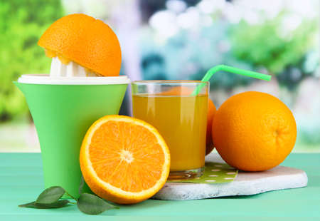 Citrus press, glass of juice and ripe oranges on green wooden table photo