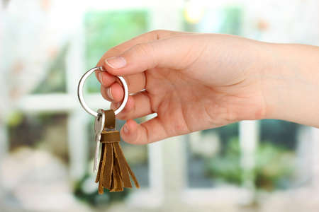 Key with leather trinket in hand on window background photo