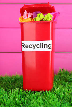 Recycling bin with papers on grass on pink background photo