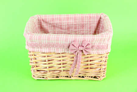Wicket basket with pink fabric and bow, on color background photo