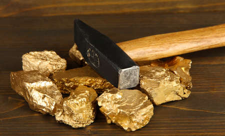 unearth: Golden nuggets with hummer on wooden background