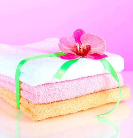 Towels tied with ribbon on light pink background photo