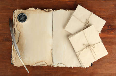 Open old book, letters and compass on wooden background Stock Photo - 19957858