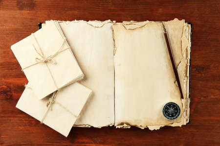 Open old book, letters and compass on wooden background Stock Photo - 19957821