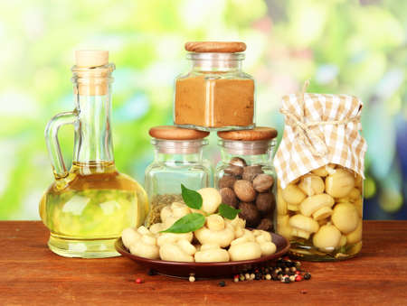wooden lid: Composition of delicious marinated mushrooms, oil and spices on wooden table on bright background
