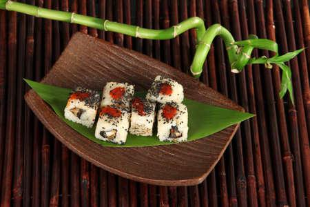 Tasty Maki sushi - Roll on plate on bamboo mat photo