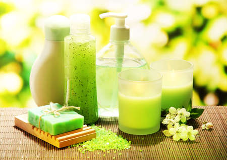 handmade soap: Cosmetics bottles and natural handmade soap on green background