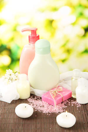Cosmetics bottles and natural handmade soap on green background photo