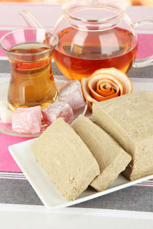 Tasty halva with tea on table close-up photo