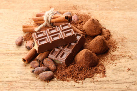 Composition of chocolate sweets, cocoa and  spices on wooden background photo