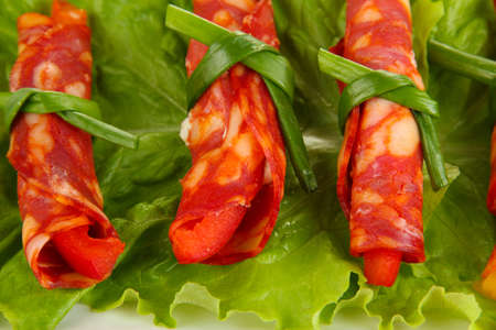 Salami rolls on green salad leaves, close up photo