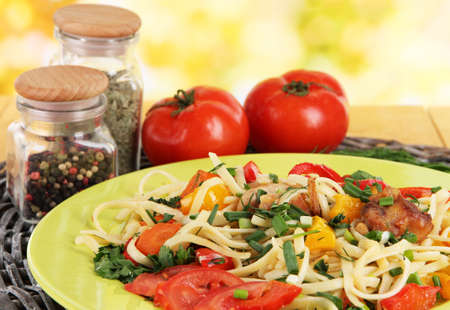 Noodles with vegetables in plates on bright background close-up photo