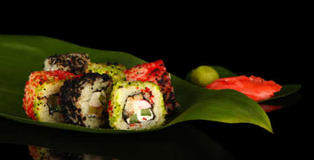 Tasty Maki sushi - Roll on green leaf on dark background photo