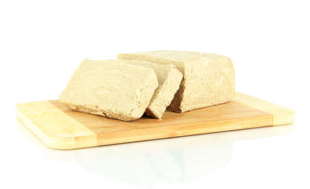 Tasty halva on cutting board isolated on white photo