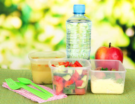 Tasty lunch in plastic containers, on bamboo mat on bright background photo