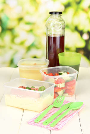 Tasty lunch in plastic containers, on wooden table on bright background photo