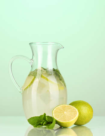 Lemonade in pitcher on turquoise background photo